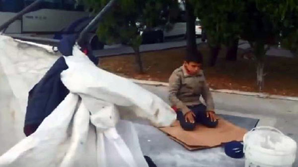 طفل سوري يصلي على الكرتون في تركيا